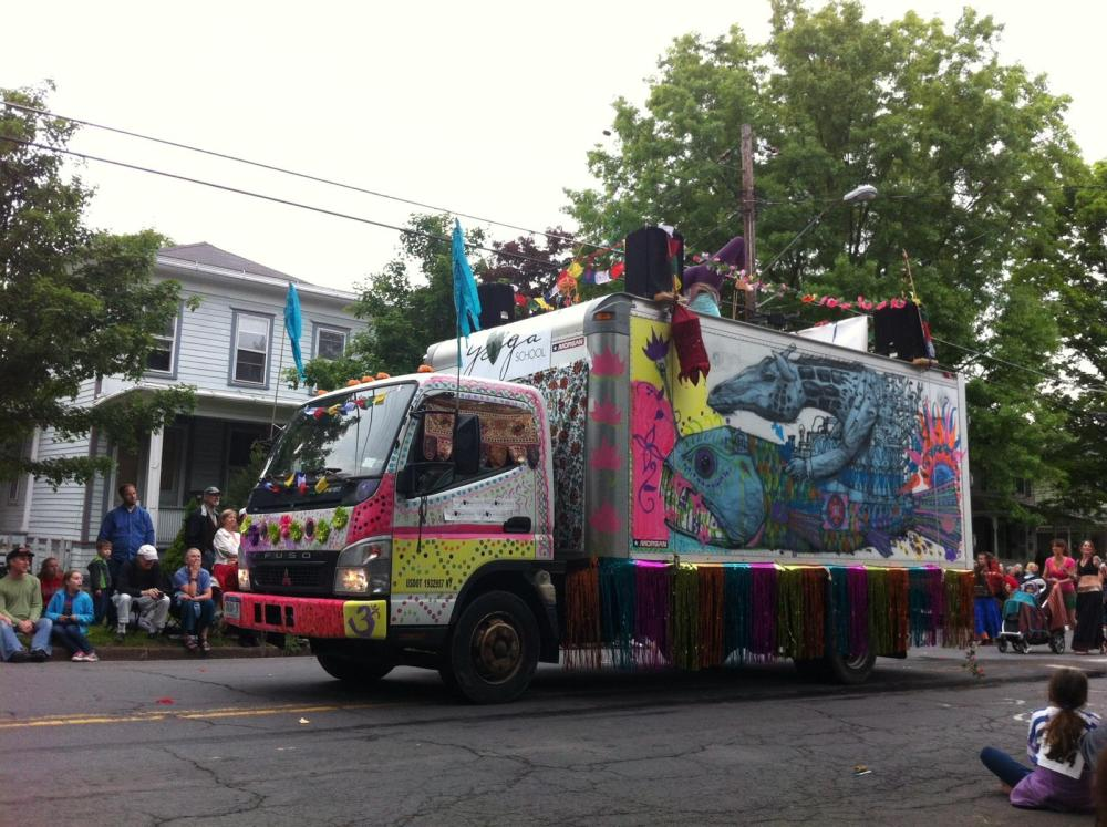 Decorated yoga truck with woman demonstrating yoga on the top; Ithaca Festival Parade, 2014